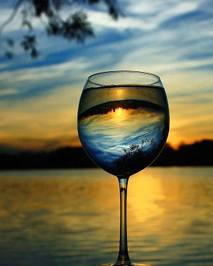wine glass with mountain and lake sunset